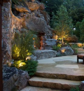 primitive looking outdoor fireplace set into boulder walls