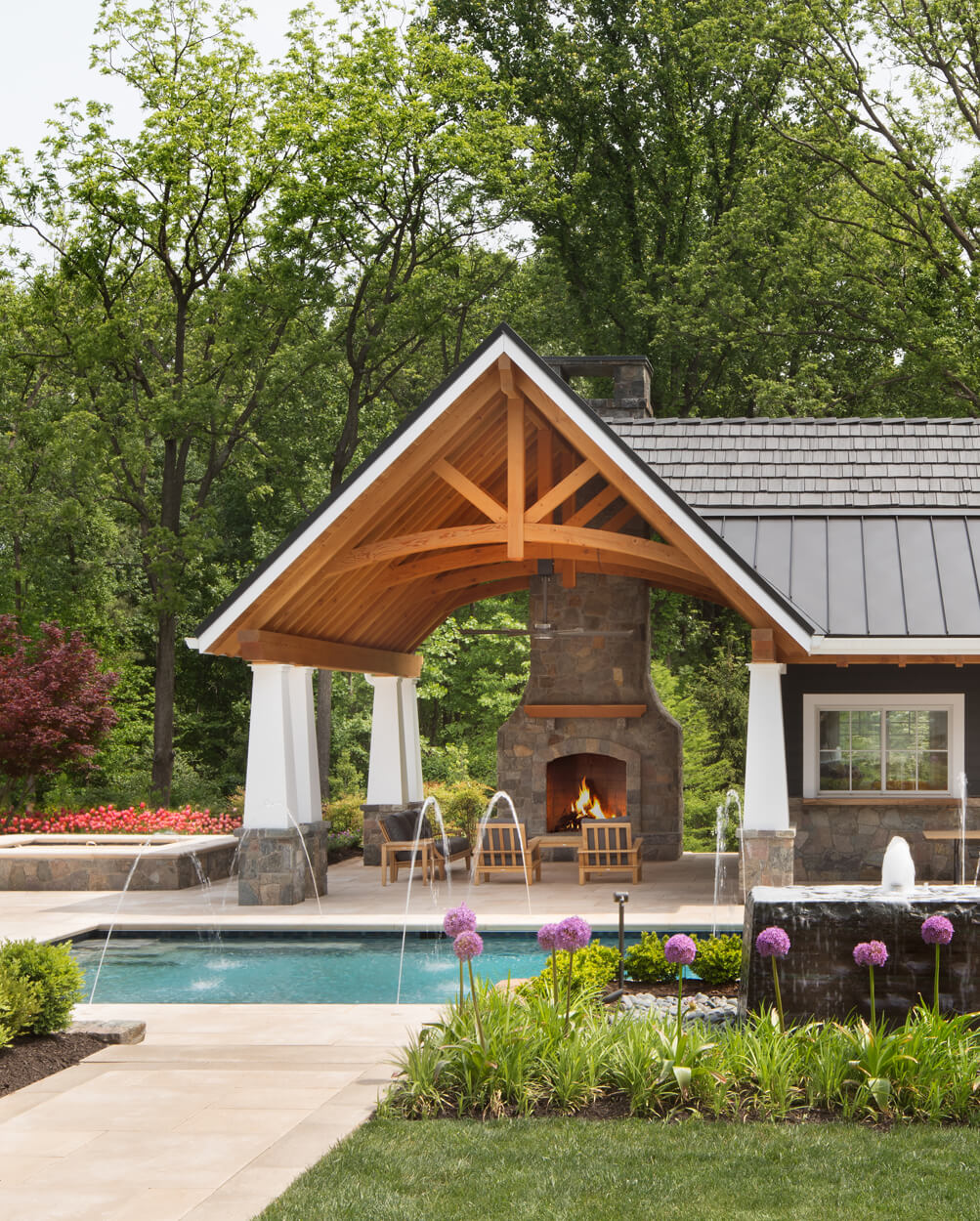 stone fireplace sheltered by poolside pavilion