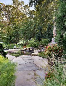 small backyard pond enclosed by lush plantings