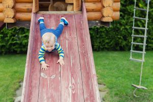 toddler going down a slide on backyard playhouse