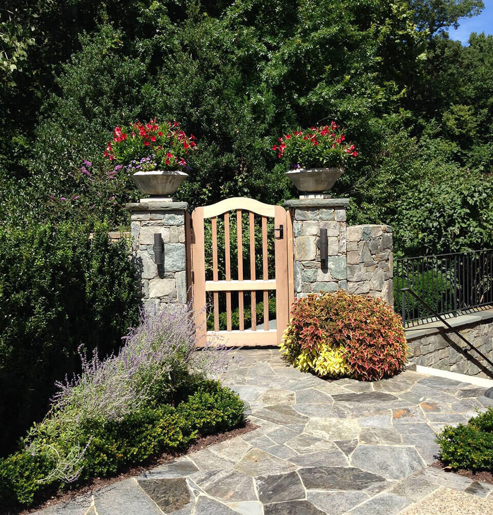 garden gate and exquisitely maintained border beds and containteer plantings