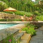 swimming pool built against retaining wall