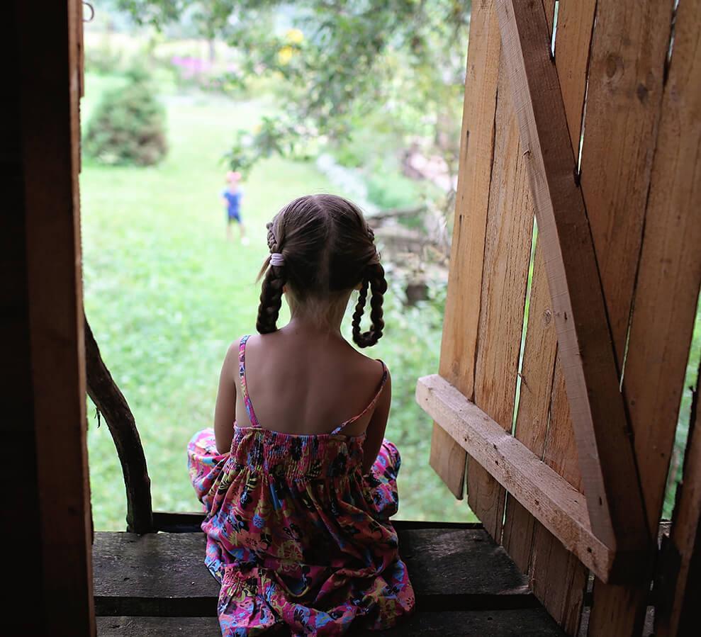 little girl sits in backyard treehouse