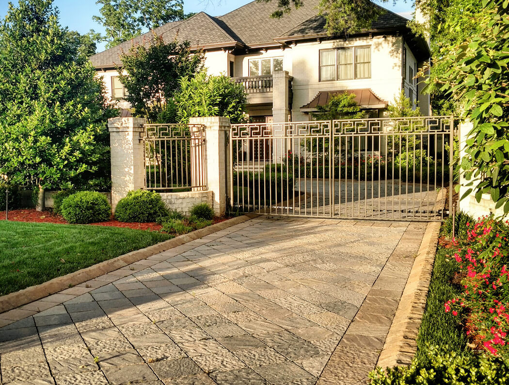 driveway with textured pavers and curb stones