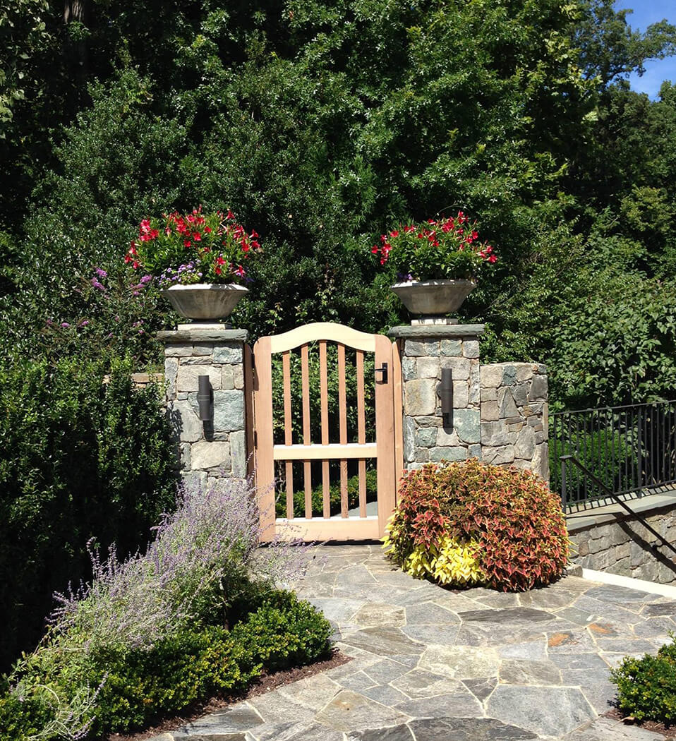 garden gate with summer with container displays of summer annuals
