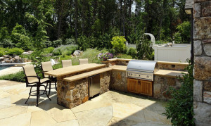outdoor kitchen with split level stone bar top