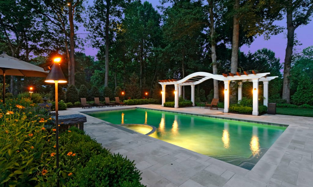 poolside pergola covering outdoor dining area