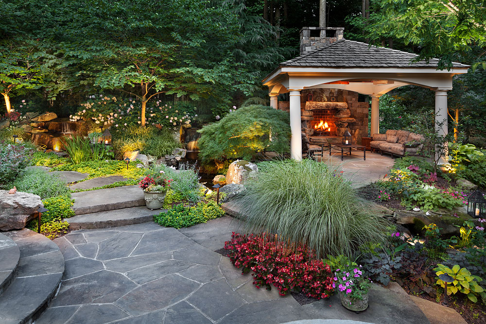 Backyard garden pergola with fireplace and lush plantings