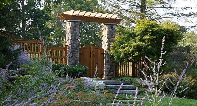 Stone wall, wooden gate with pergola