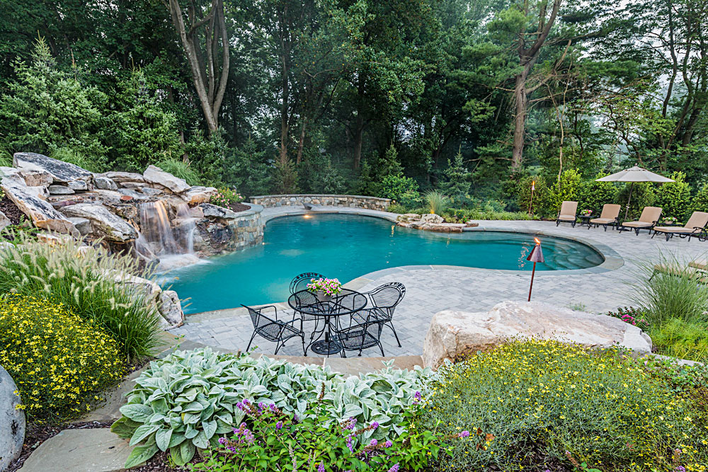Clover leaf pool with boulders and lush plantings