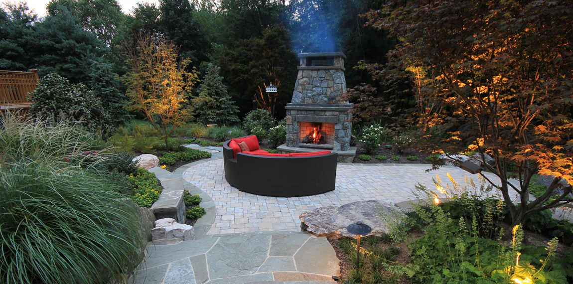 Outdoor living room with rustic stone fireplace by Surrounds