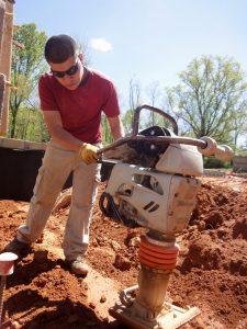 landscape construction tech using soil compactor