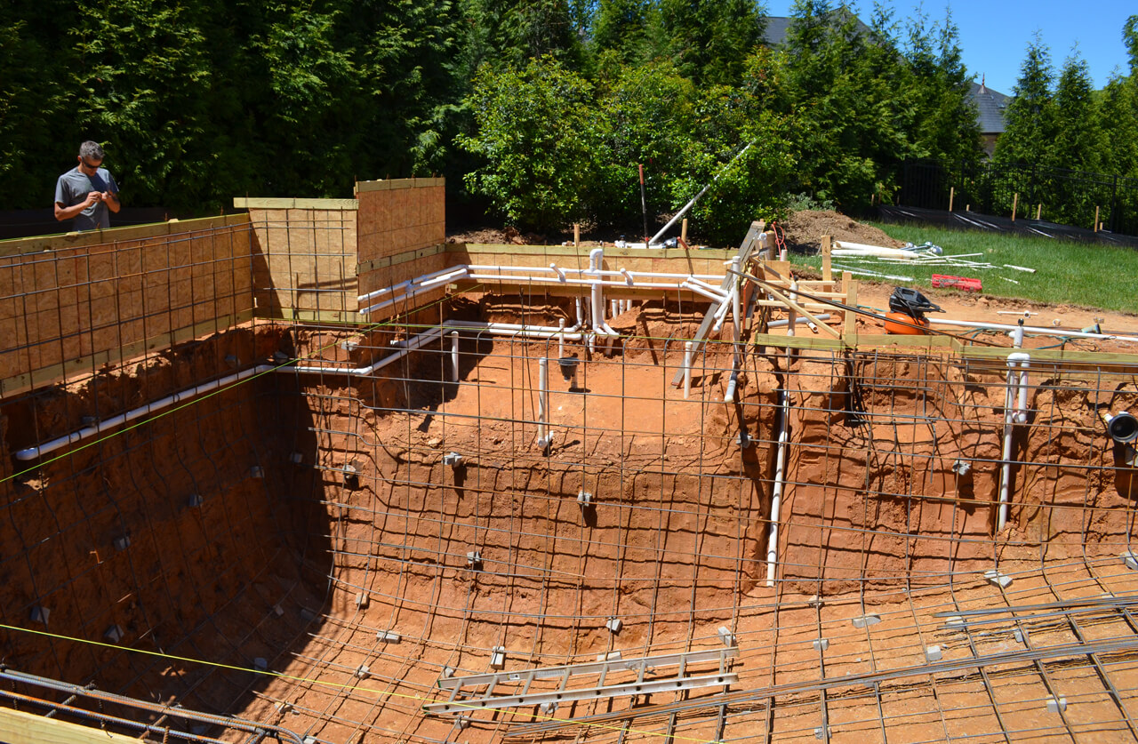 inground pool excavation showing rebar grid prep for gunite spray