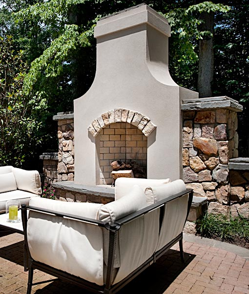 Outdoor fireplace with stucco and stone arch