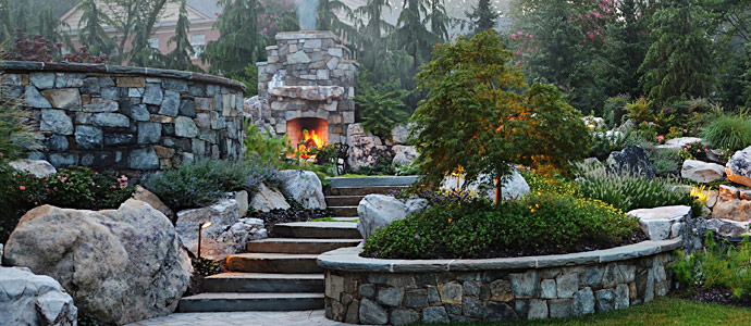 Our landscape architects design outdoor fireplaces & fire pits that invite you to sit in the garden long past twilight to enjoy warmth