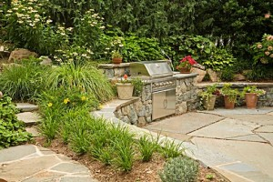 Outdoor kitchen grill built into retaining wall