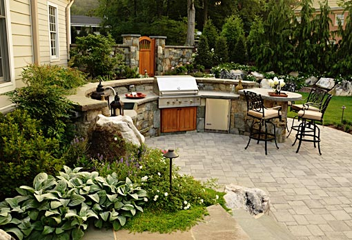 Outdoor kitchen with split level countertop and bar