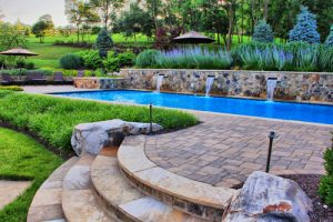 swimming pool with water spouts retaining wall
